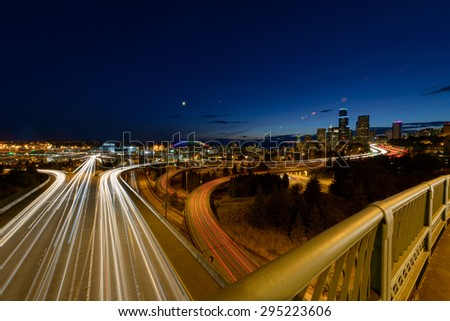 City skyline at night with car lights streaking on highway - stock photo