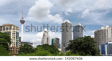 City skyline of Kuala Lumpur city against an urban green park and blue cloudy sky.  - stock photo