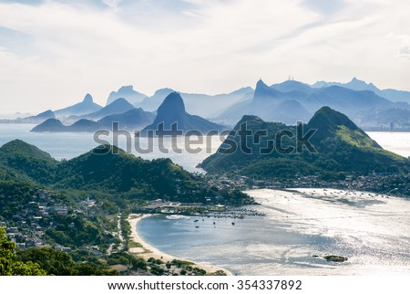 City skyline scenic overlook of Rio de Janeiro, Brazil with Niteroi, Guanabara Bay, and Sugarloaf Mountain backlit in afternoon sun - stock photo