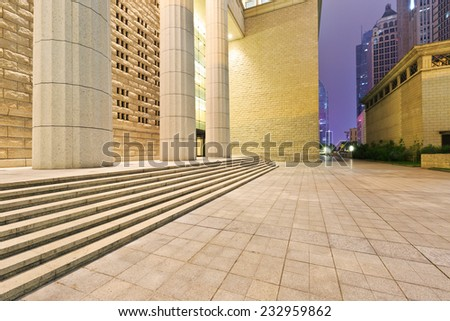 City square in front of the modern building at night - stock photo