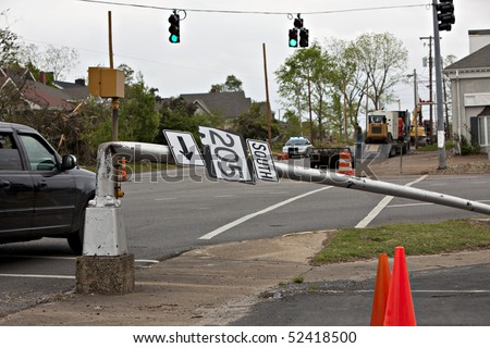 City street after tornado showing light pole bent at 90 degrees - stock photo