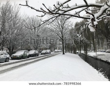 City street and cars covered with snow
