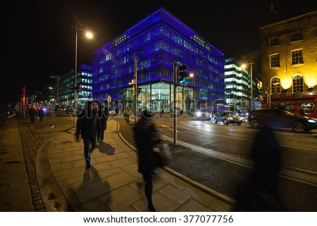 City Street busy with pedestrians and office buildings during the night. Dublin - stock photo