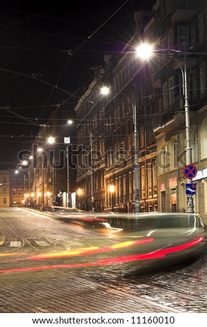 City street in the night with blurred cars and traffic lights - stock photo