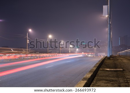 City street, lampposts and glowing stripes. Night view