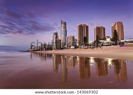 city tall towers rising from coastline sand and beach in Surfers paradise at Gold Coast Queensland Australia at sunrise with reflection of towers on wet water - stock photo