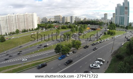City traffic on crossroad at summer cloudy day. Aerial view - stock photo