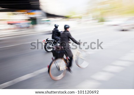city traffic with a cyclist and a motorcyclist in motion blur - stock photo