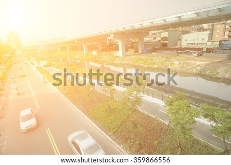 City traffic with cars motion blurred on road near bridge on river in daytime in Taipei, Taiwan, Asia. - stock photo