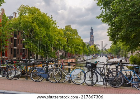 City view of Amsterdam canal, church Westerkerk and typical houses, boats and bicycles, Holland, Netherlands.