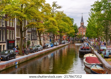 City view of Amsterdam canals and typical houses, boats and bicycles, Holland, Netherlands. - stock photo