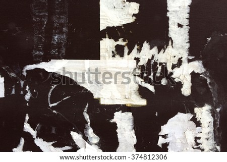 City wall with torn paper advertising. Grunge urban texture. Messy bulletin board  - stock photo