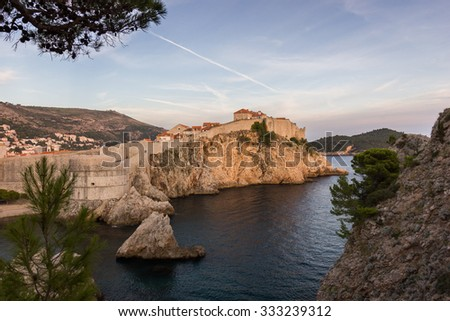 City Walls on a steep cliff at the Old Town in Dubrovnik, Croatia, at sunset. - stock photo