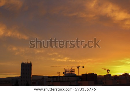 City with crane in sunset