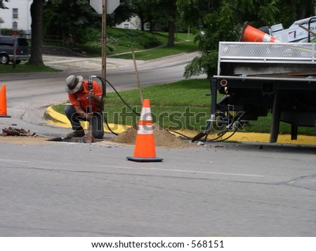 City worker repairs utilities under the street - stock photo