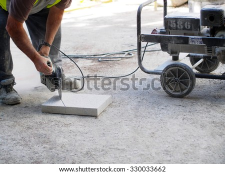 City workers - disc grinder and paving slab