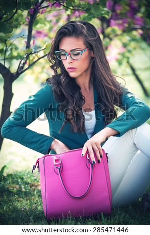 city young woman with fashion accessories. bag and eyeglasses, outdoor in park - stock photo