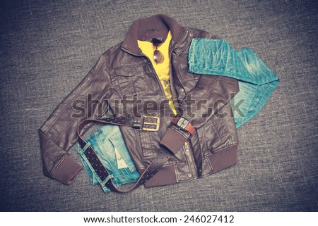 City youth fashion clothing. Brown jacket, blue jeans, T-shirt, belt, watches and sunglasses. Photo toned in vintage style - stock photo