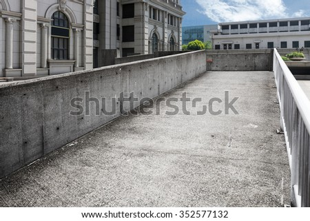 cityscape and empty concrete footpath by modern building in cloudy sky