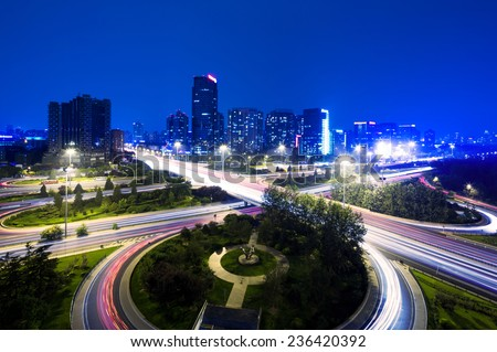cityscape and traffic trails of beijing at night - stock photo