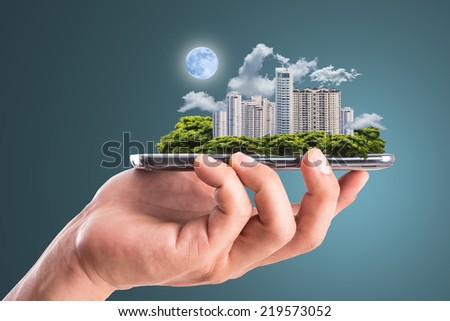 Cityscape ,hold smart phone for build and make your green city. - stock photo