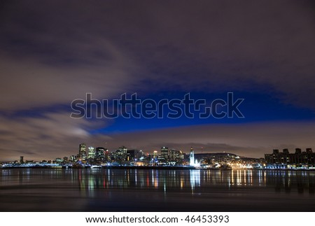 cityscape night scene Montreal Canada over river Saint Lawrence impressive and vibrant dusk sky skyscrapers lights - stock photo