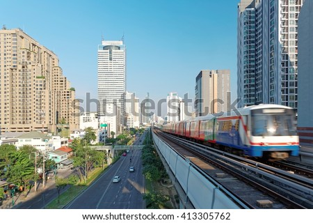 Cityscape of Bangkok, the fast developing capital city of Thailand, with view of a rapid BTS train traveling on elevated rail system between high rise skyscrapers in downtown on a beautiful sunny day
