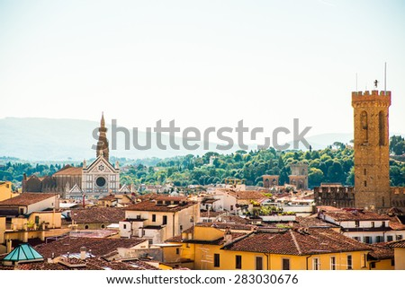 Cityscape of Florence on sunny day with multiple tiled roofs and historical monuments. Basilica di Santa Croce is visible in distance. - stock photo