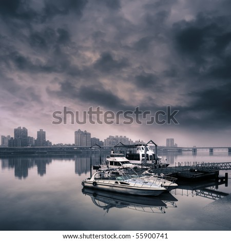 Cityscape of harbor with boat on water against dramatic sky. - stock photo