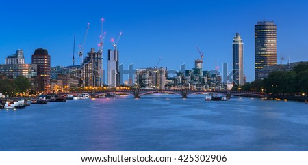Cityscape of London with reflection in Thames river at night, UK