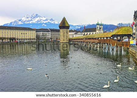Cityscape of Lucerne with Chapel Bridge and Jesuit Church in Switzerland. Mount Pilatus overlooking Lucerne visible in the background - stock photo