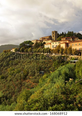 Cityscape of Montecatini, Italy.  The upper old city sits at the top of the mountain showing the olive groves - stock photo