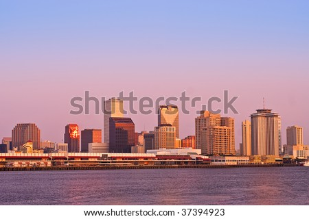 Cityscape of New Orleans CBD from across Mississippi River; buildings lit by sunrise