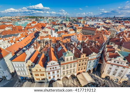 Cityscape of Prague, Czech Republic. View on traditional red roof tenement houses as seen from Old Town City Hall. Blue sunny sky, wide angle skyline - stock photo