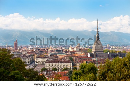 Cityscape of Turin (Italy) featuring the Mole Antonelliana and the Alps in the background.