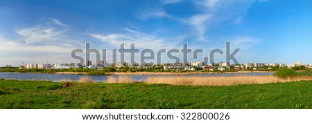 Cityscape on green grass and blue sky