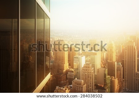 Cityscape reflected in the glass of an office building at sunset - stock photo