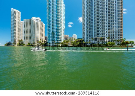 Cityscape view of downtown Miami along the Miami River inlet with Brickell Key in the background and boat and jet ski cruising by. - stock photo