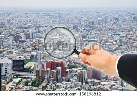 cityscape view through magnifying glass - stock photo