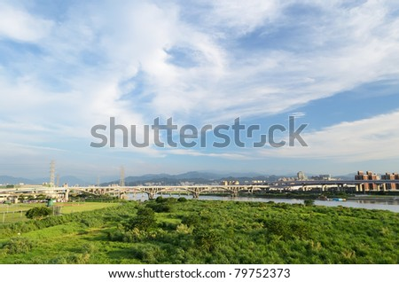 Cityscape with green forest under dramatic blue sky and white clouds in Taipei, Taiwan, Asia. - stock photo