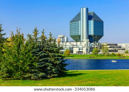 Cityscape with Office Building and Park with Green Grass near Blue Lake
