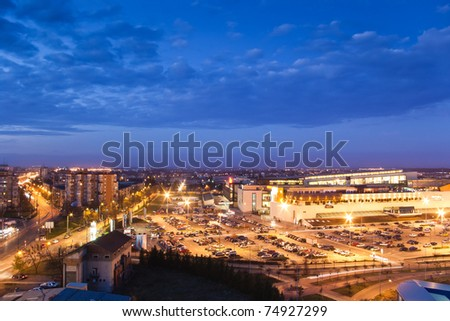 cityscape with parking and mall after sunset
