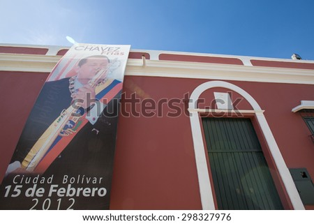 CIUDAD BOLIVAR, VENEZUELA, APRIL 9: Poster of Hugo Chavez President of Venezuela celebrating the 15th of February hanging on the facade of an old colonial building in Ciudad Bolivar, Venezuela 2015. - stock photo