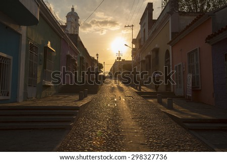 CIUDAD BOLIVAR, VENEZUELA, APRIL 9: Sunset in old colonial street with a unrecognizable man walking, very typical view of Ciudad Bolivar with its old street stairs in Venezuela. April 9, 2015. - stock photo