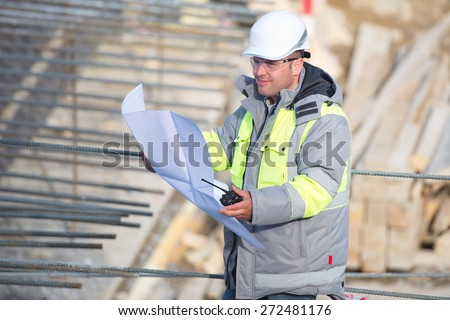 Civil Engineer at at construction site is inspecting ongoing production according to design drawings. - stock photo