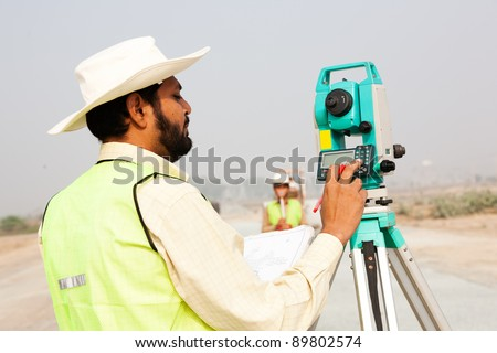 civil engineer working at a construction site, surveyor doing the survey at construction site - stock photo