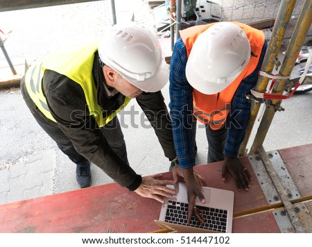 Civil engineers at work with computer laptop on construction site. View from above