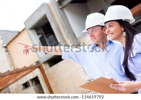 Civil engineers working in a construction site and pointing away - stock photo