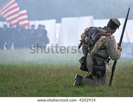 Civil War action as lone Soldier drops to knees to meet his fate as smoke from Muskets rises - stock photo