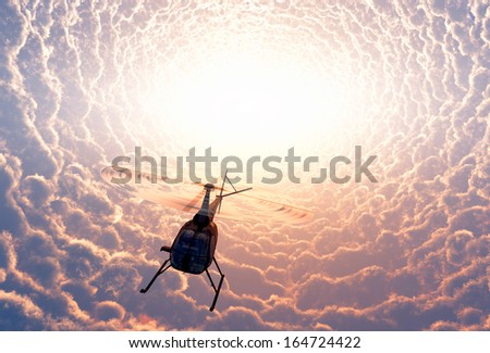 Civilian helicopter of mystical clouds. - stock photo